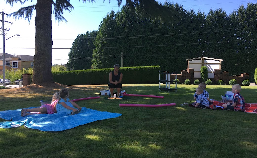 Liz Tolkamp teaches an outdoor Sunday school class for ages 3-5. Each family pre-registered and sat on their own designated blanket during the class.
