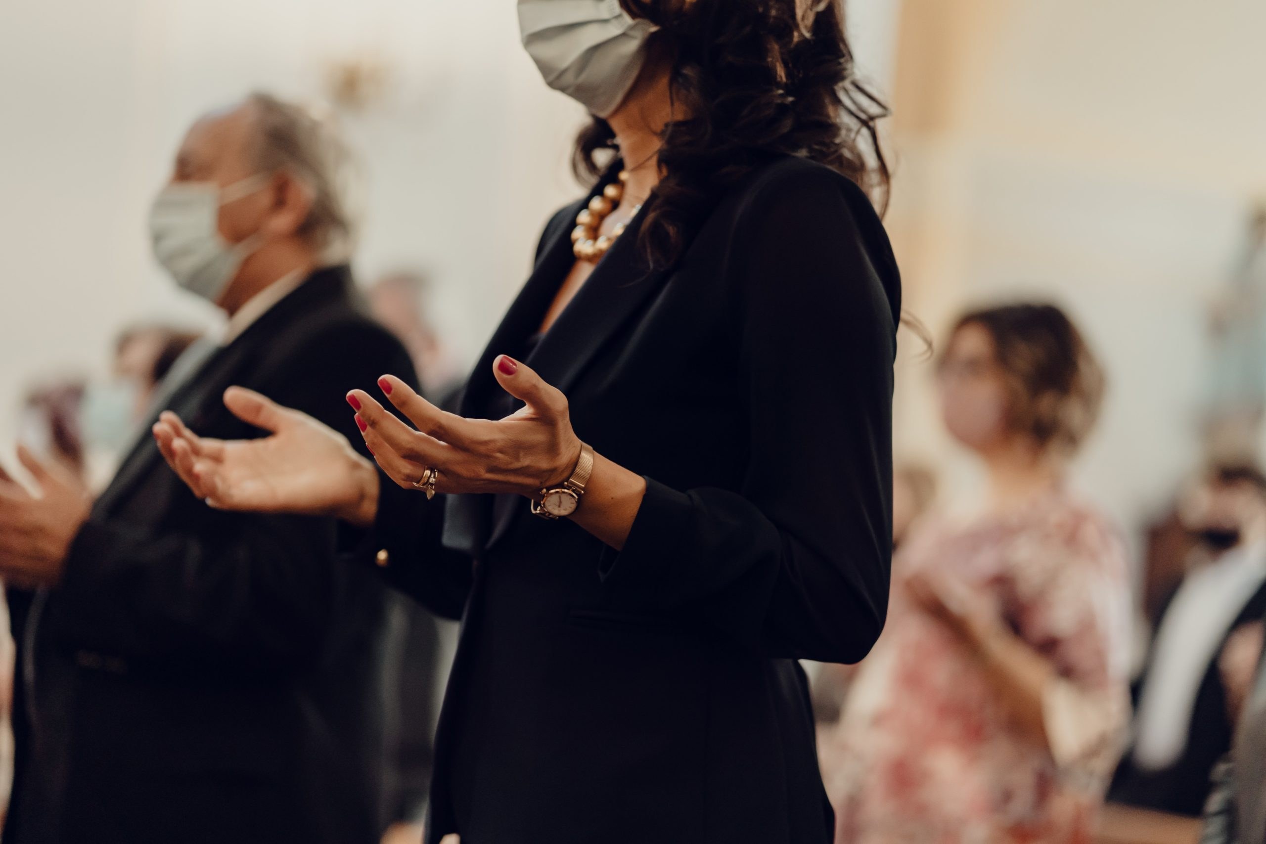 Woman lifting hands in church with mask on.