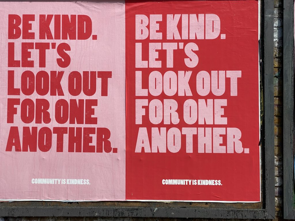 Pink sign saying 'Be kind. Let's look out for one another.'