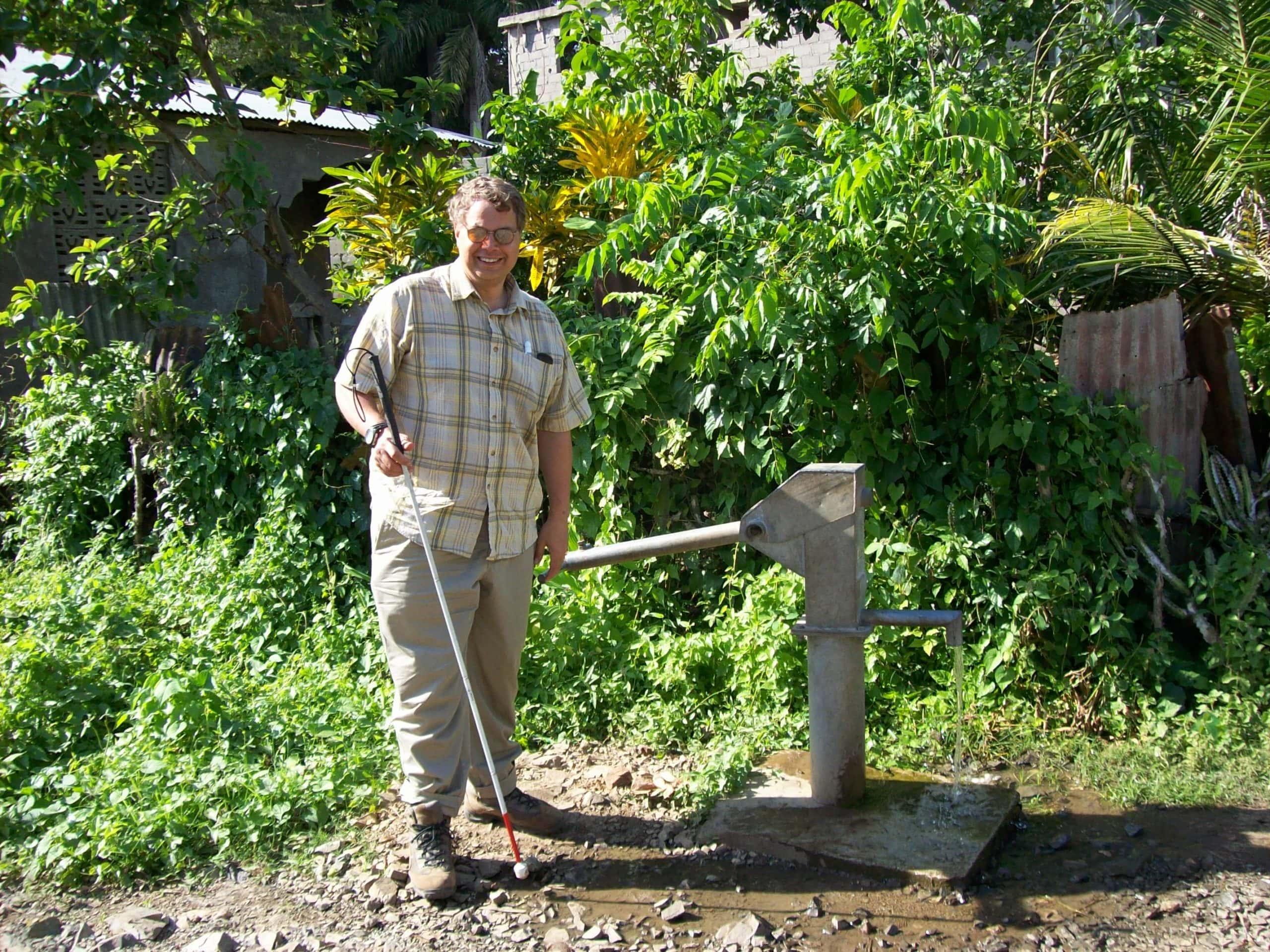 Man standing at water pump