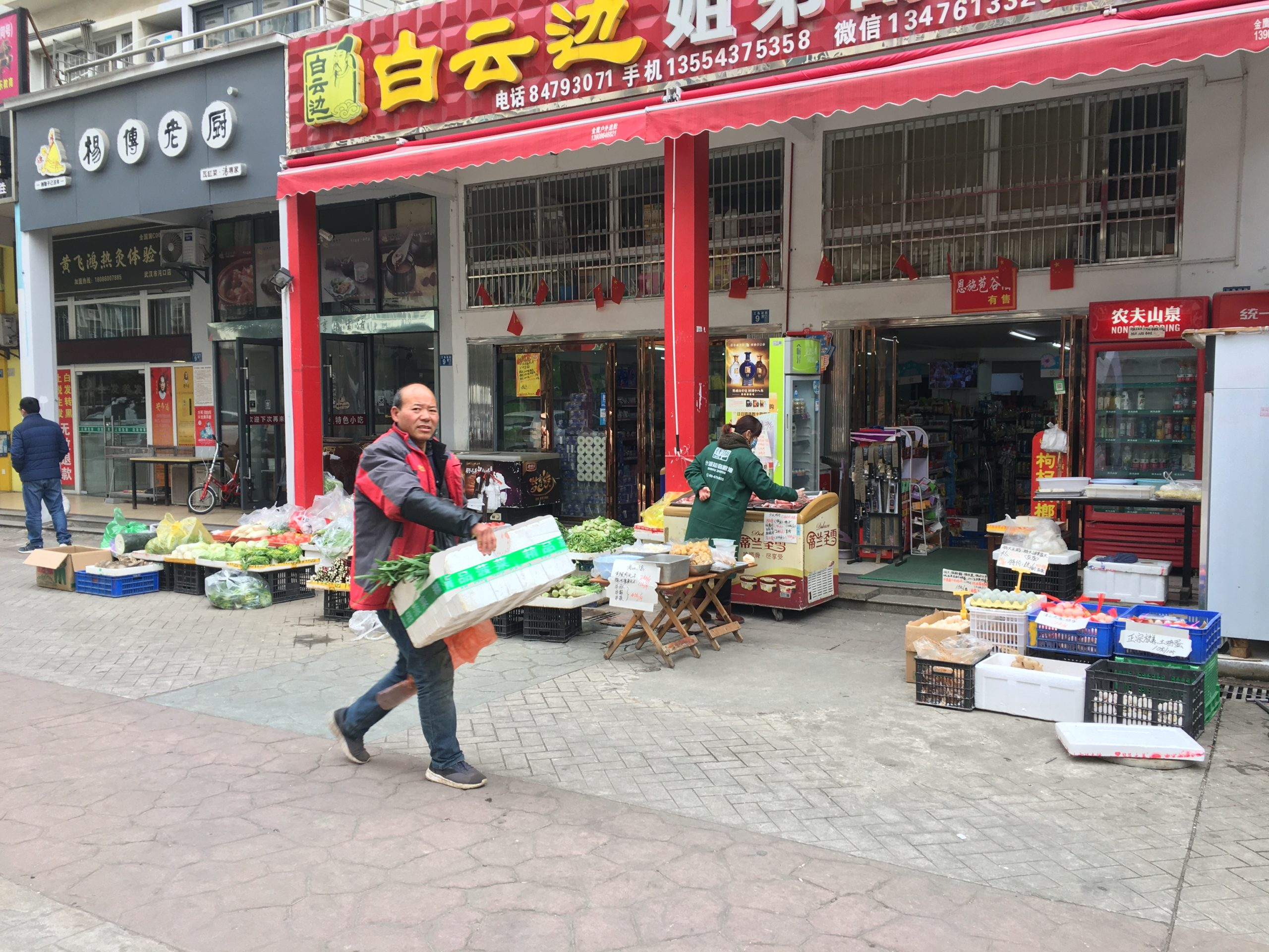 Man carrying a box past shops.