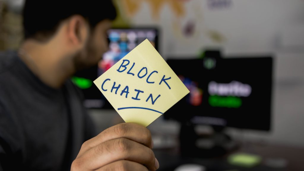 man holding sticky note saying 'block chain'