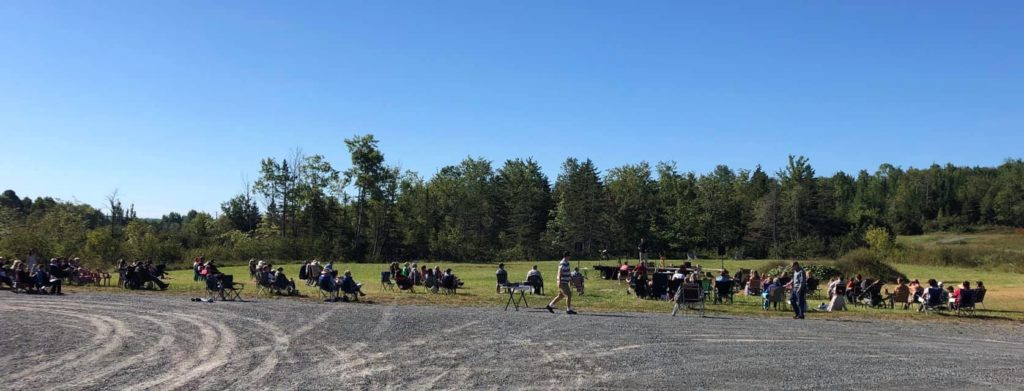 People spread out on camp chairs in a panorama shot.