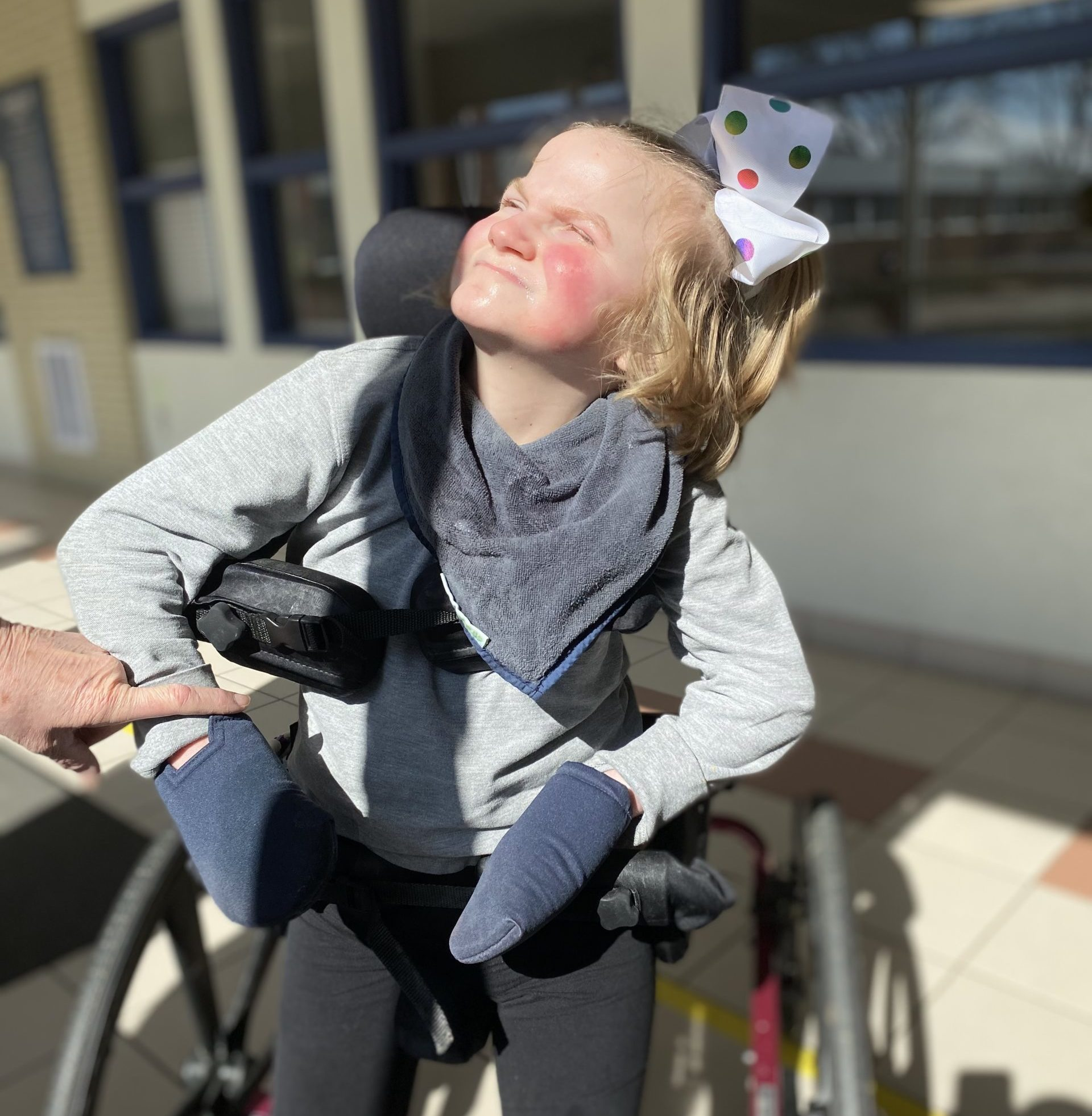 A girl in a wheelchair with her face up towards the sun.
