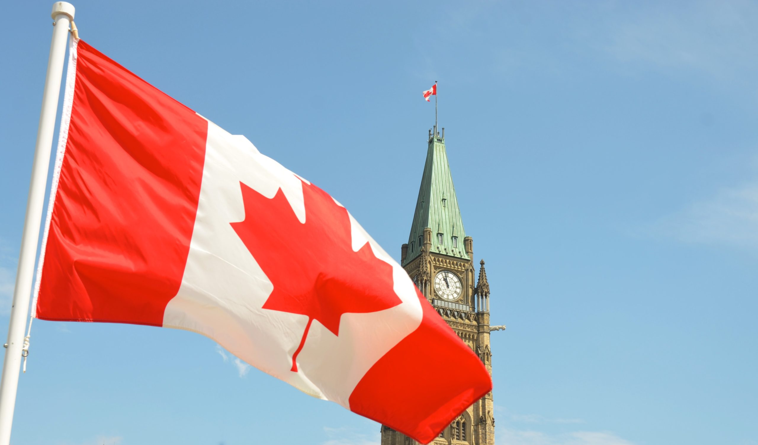 A Canadian flag outside of Parliament building.