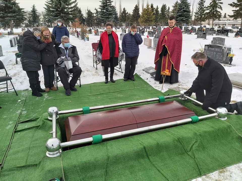 A group of people standing distanced around a casket.