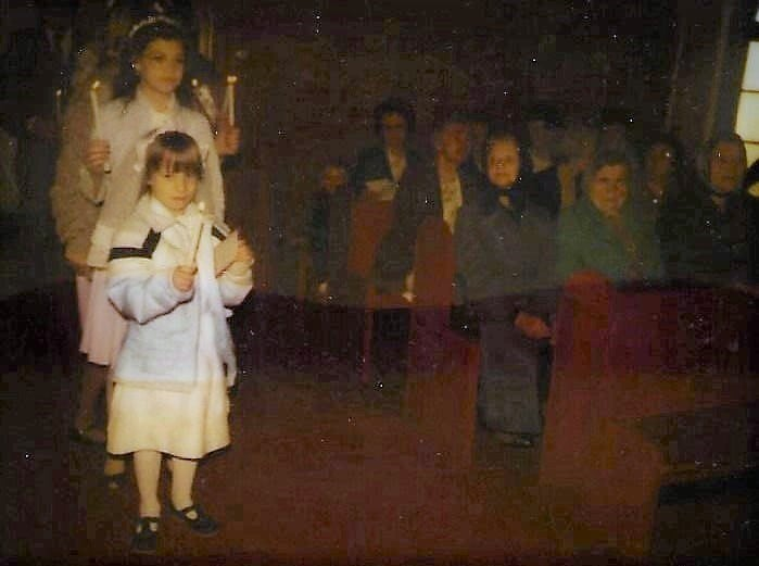 a girl with a lighted candle standing in church