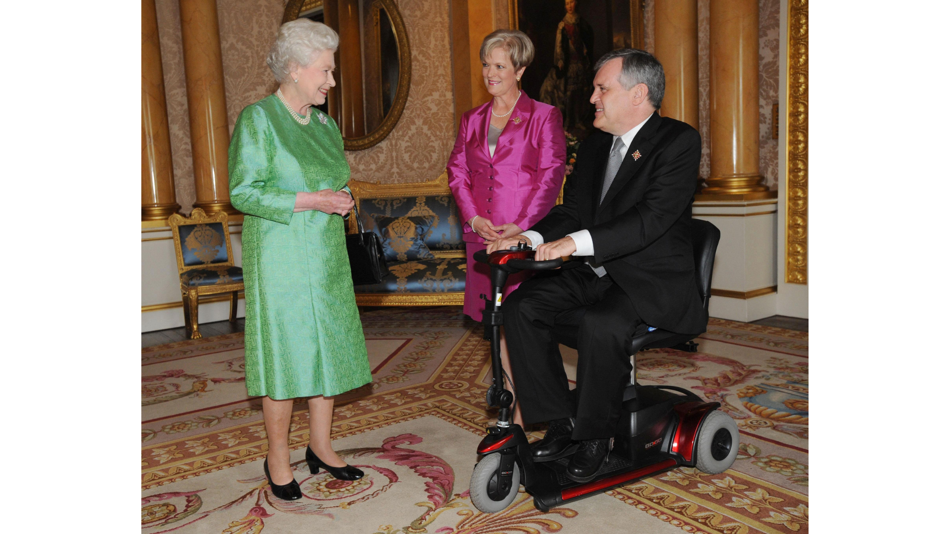The Queen smiles at David Onley, a man in a wheelchair, in a carpeted room