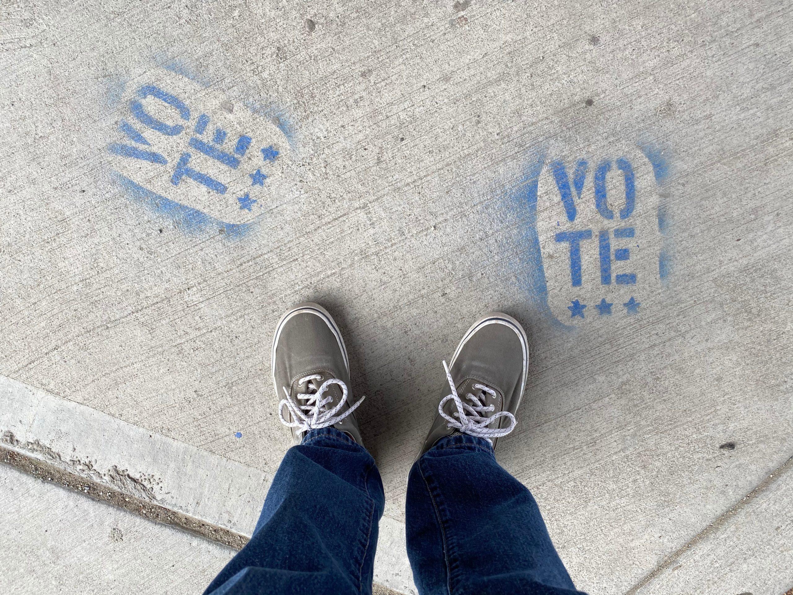 feet by vote signs on the sidewalk