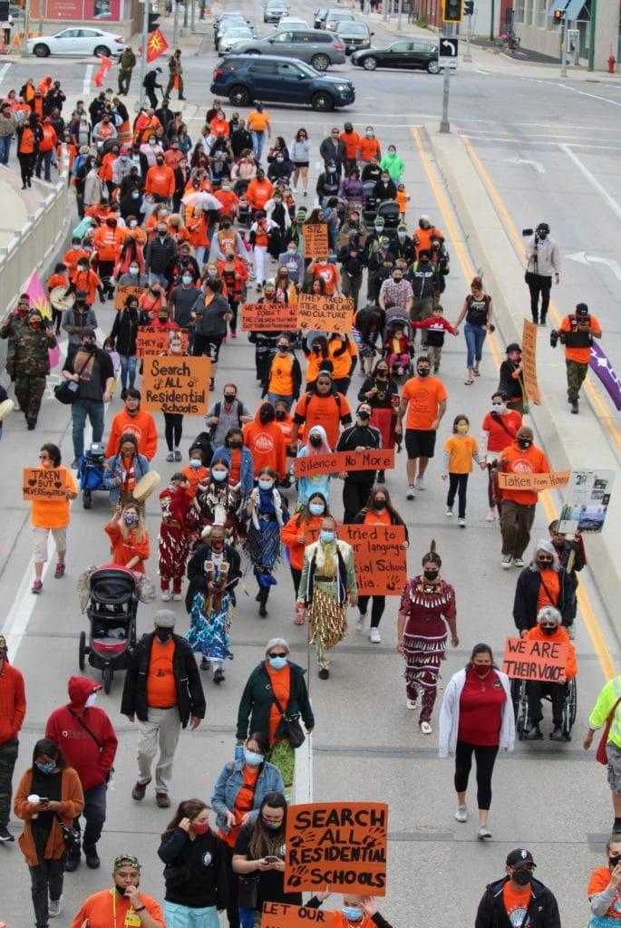 a crowd of people dressed in orange walking down the street